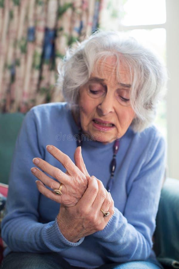 Ältere Frau zu Hause, die mit Arthritis leidet stockfotografie