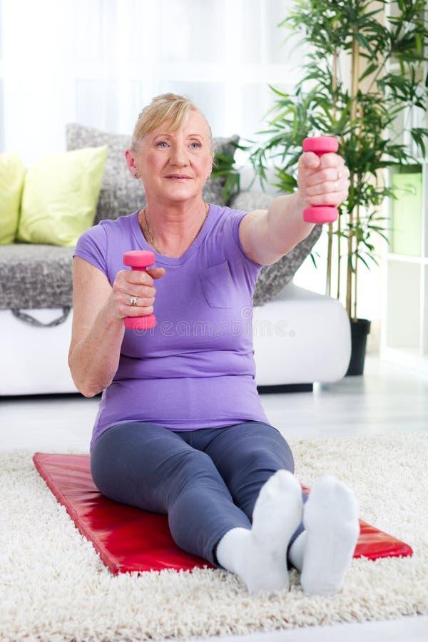 Ältere Frauenübung mit Gewichten zu Hause stockfoto