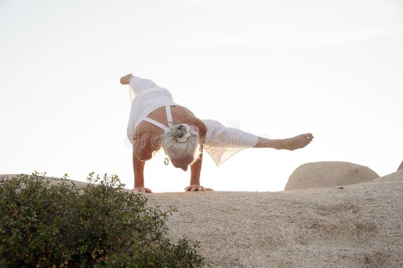 Ältere Frauen-Arm-Balance auf Stein lizenzfreies stockfoto