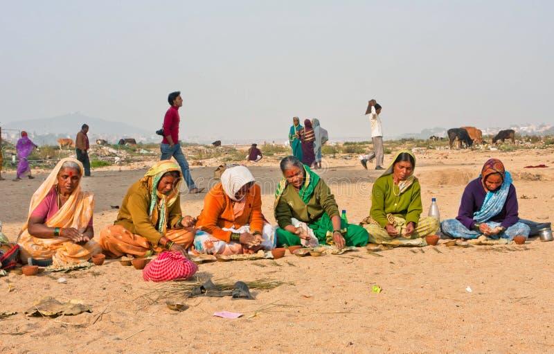 Ältere Frauen bereiten prasadam zu einer religiösen Feier in einer Wüste vor stockfotografie
