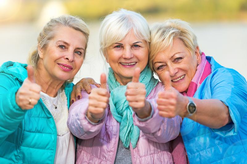 Ältere Frauen, die sich Daumen zeigen stockfotos