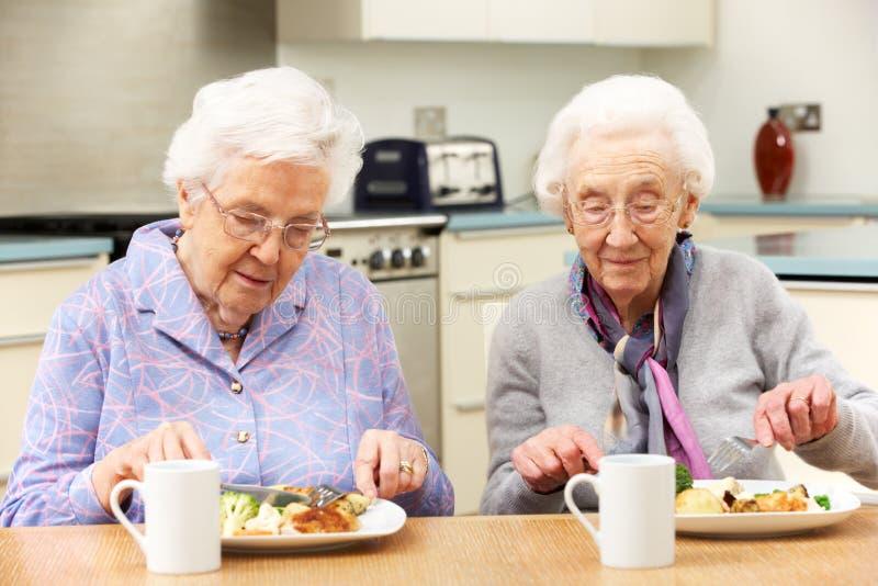 Ältere Frauen, die zusammen Mahlzeit zu Hause genießen lizenzfreie stockbilder