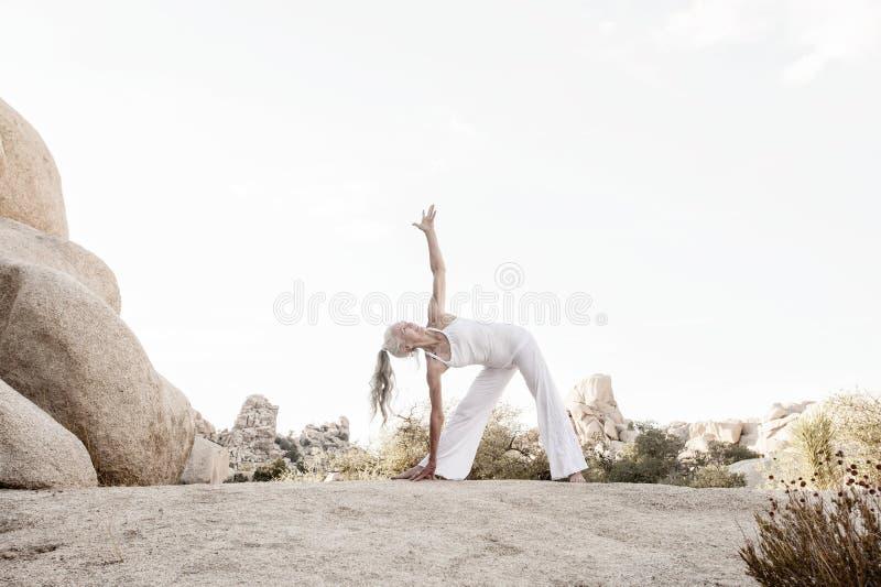 Ältere Frauen-Dreieck-Yoga-Haltung auf Stein stockfotografie