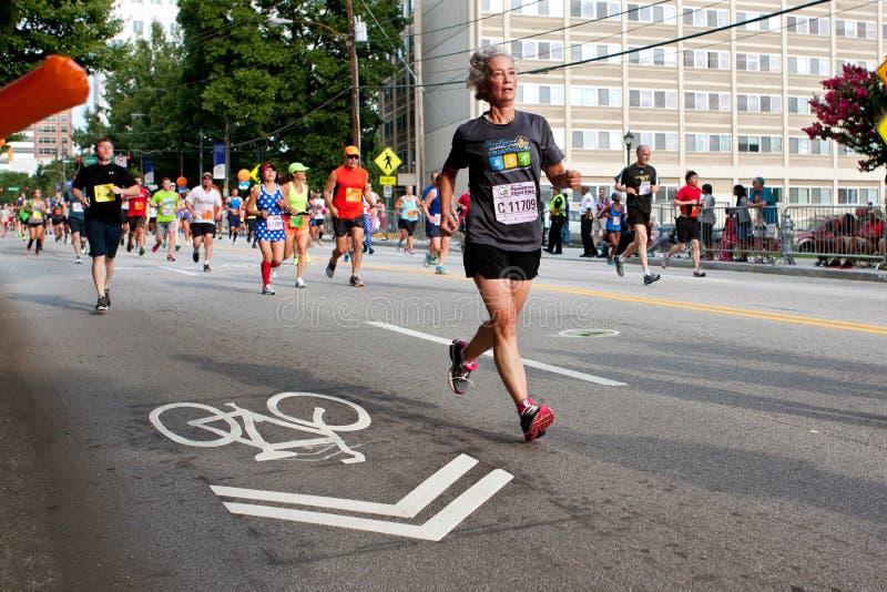 Ältere Frauen-Läufe in Straßenrennen Atlantas Peachtree stockbilder