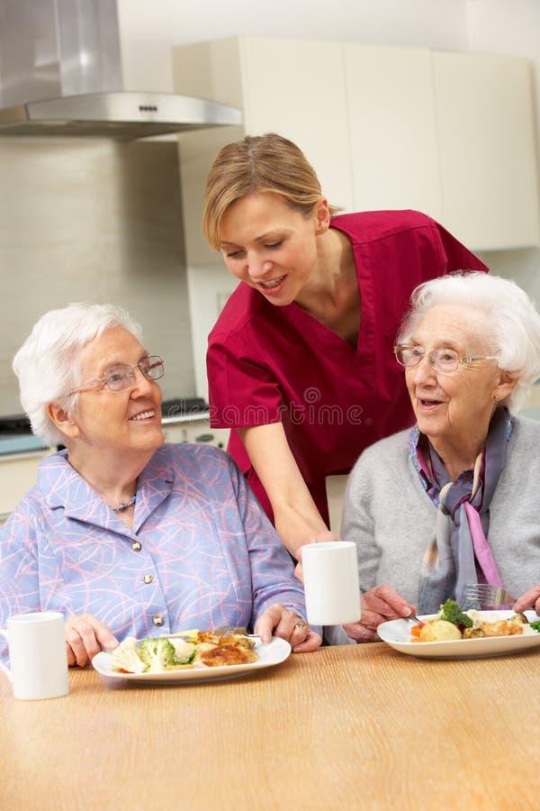 Ältere Frauen mit dem Betreuer, der zu Hause Mahlzeit genießt stockbild