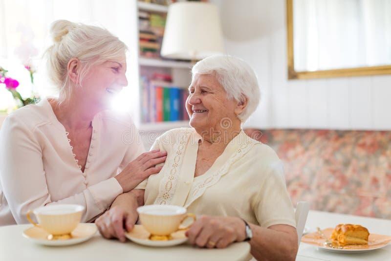 Ältere Frauenausgaben-Qualitätszeit mit ihrer Tochter stockfotos