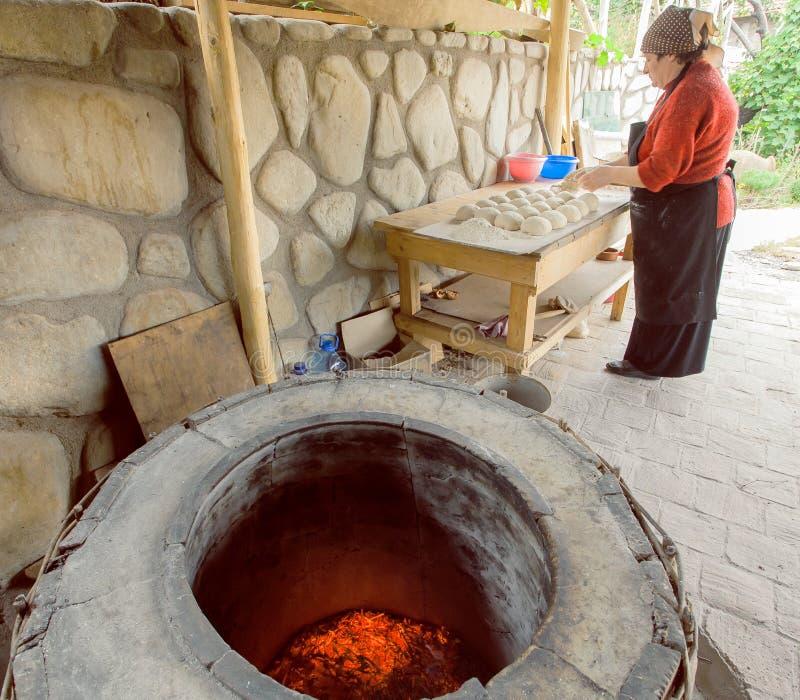 Ältere Frauenbackentorten in ihrer Hauptküche in der georgischen Dorfart mit Lehmofen stockbild