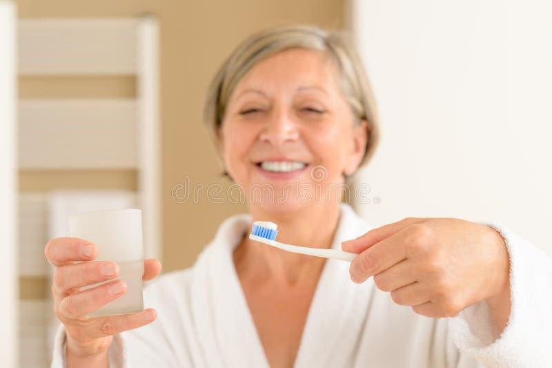 Ältere Fraueneinflußzahnbürste und Glaswasser stockfoto