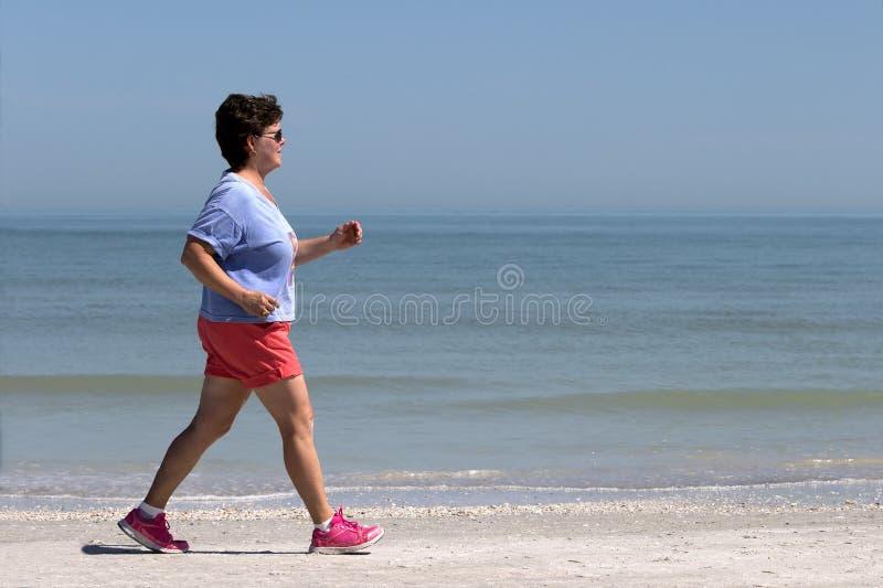 Ältere Frauenenergie, die auf einen Strand geht lizenzfreies stockfoto
