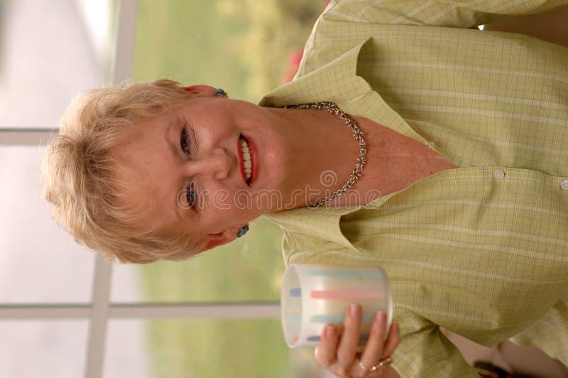 Ältere Frauenholdingmilch lizenzfreie stockfotografie