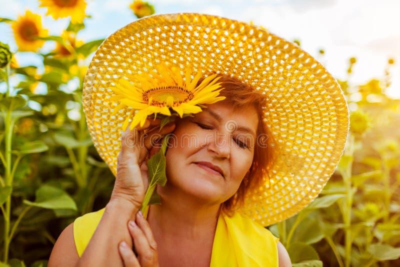 Ältere Frauenholdingsonnenblume auf dem Sommergebiet, das Natur genießt Gl?ckliche Frau, die sich drau?en entspannt lizenzfreies stockfoto