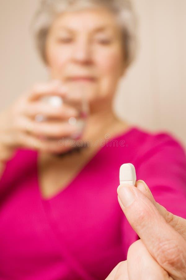 Ältere Frauenholdingtablette oder -pille mit Wasser lizenzfreie stockbilder