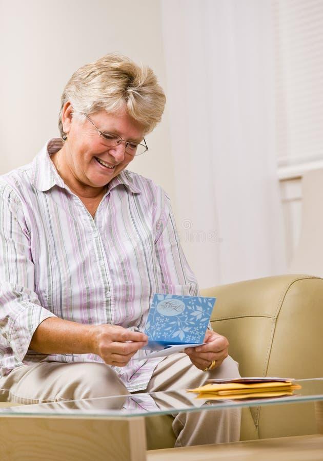 Ältere Frauenleseanmerkungskarte stockfotografie