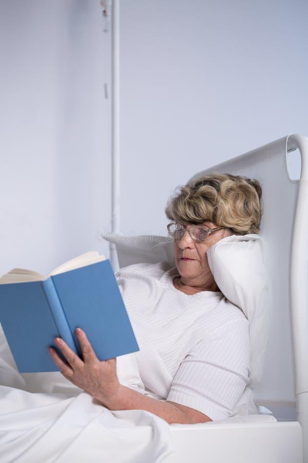 Ältere Frauenlesung im Bett lizenzfreie stockfotos