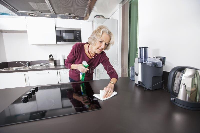 Ältere Frauenreinigungsküchenarbeitsplatte lizenzfreies stockbild