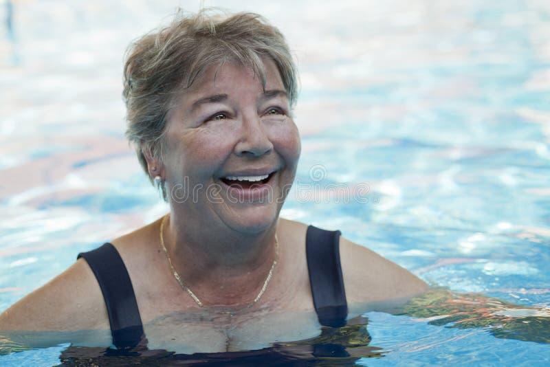 Ältere Frauenschwimmen am Pool stockfoto