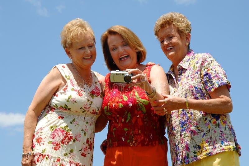 Ältere Freunde, die Foto überprüfen lizenzfreie stockbilder