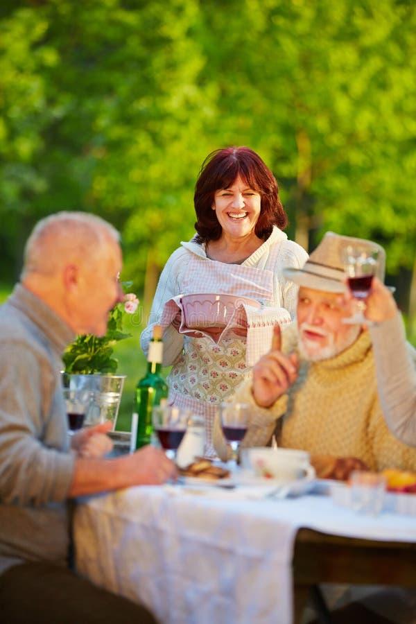 Ältere Freunde, die Geburtstag im Garten feiern stockfoto