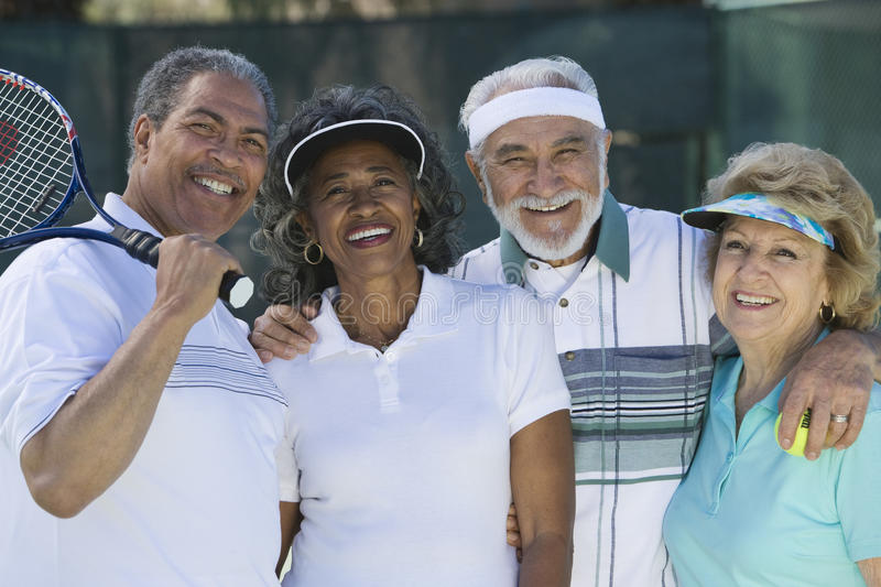 Ältere Freunde am Tennisplatz lizenzfreies stockbild