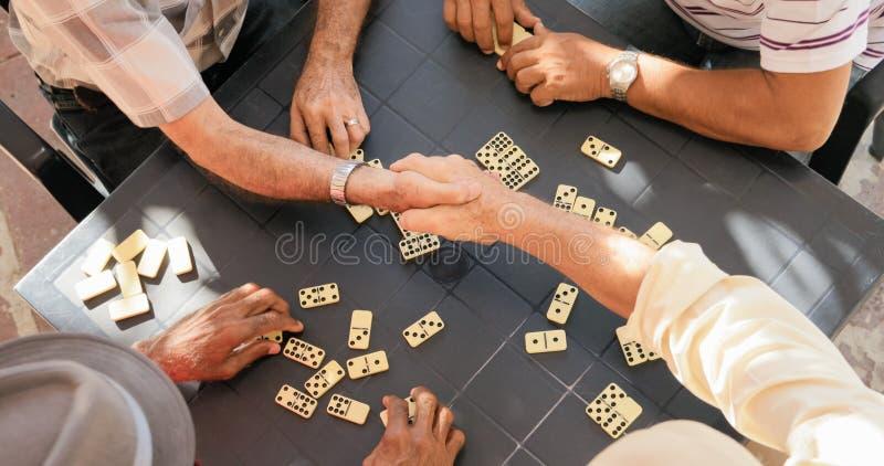 Ältere Freunde, welche die Hände gewinnen Spiel des Dominos rütteln lizenzfreies stockfoto