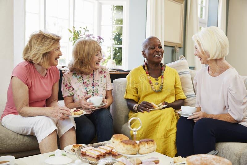 Ältere Freundinnen, die zu Hause Nachmittagstee zusammen genießen lizenzfreie stockfotos