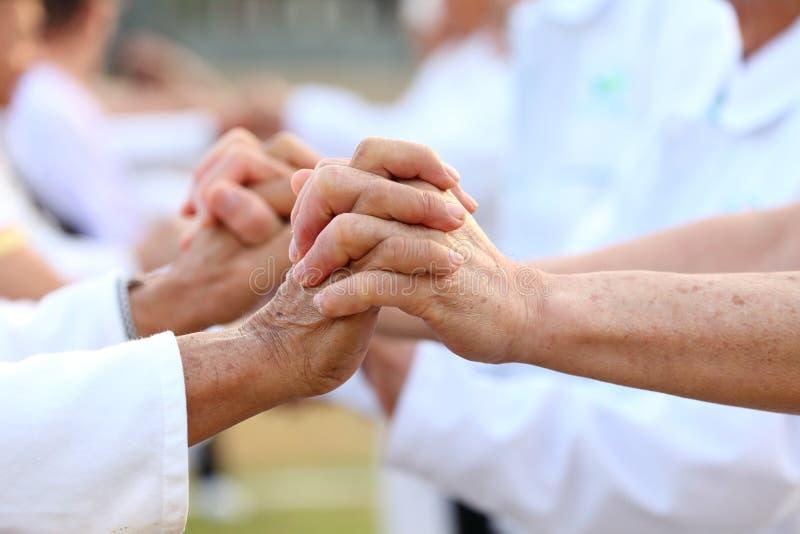 Ältere geduldige Leute schließen sich Hand zusammen an und stützen sich, um das Leben der guten Gesundheit anzuregen lizenzfreie stockbilder