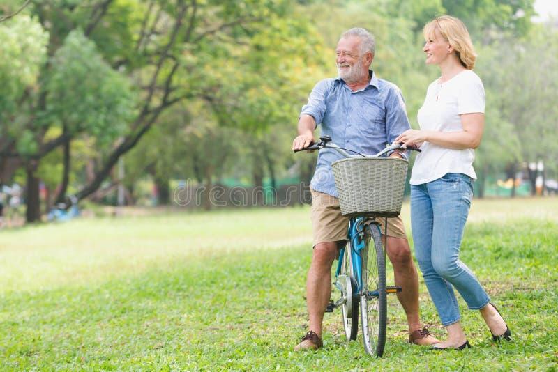Ältere gehende Paare ihr Fahrrad stockfotos