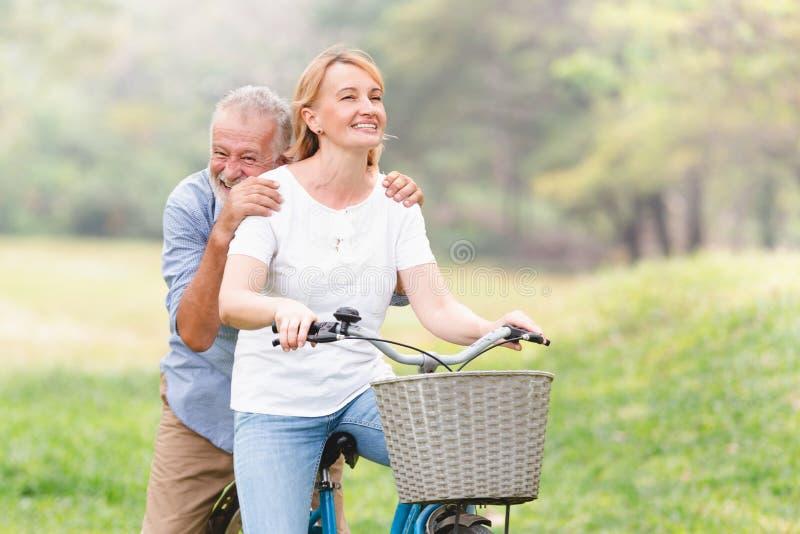 Ältere gehende Paare ihr Fahrrad lizenzfreie stockfotos