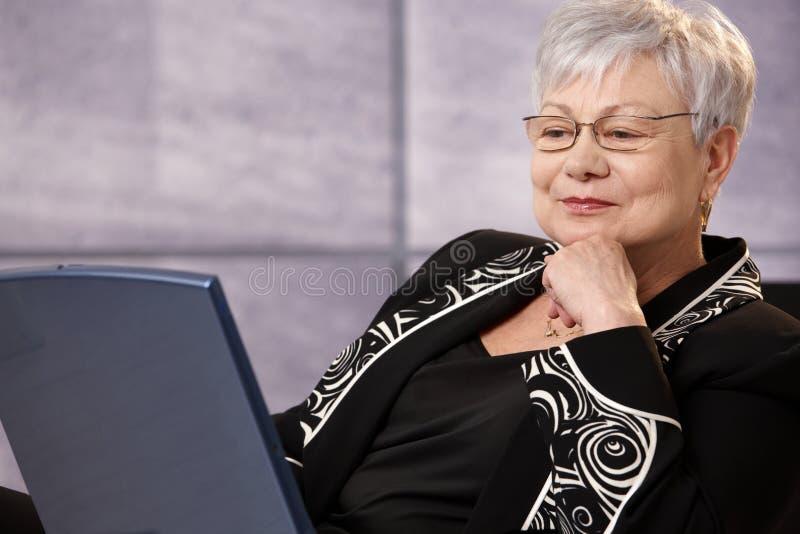 Ältere Geschäftsfrau, die Bildschirm betrachtet stockbild