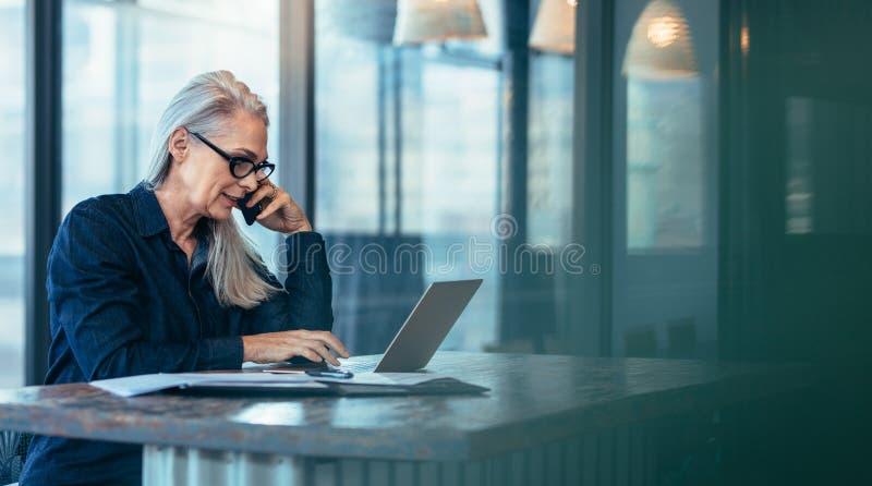 Ältere Geschäftsfrau, die am Handy spricht stockbild