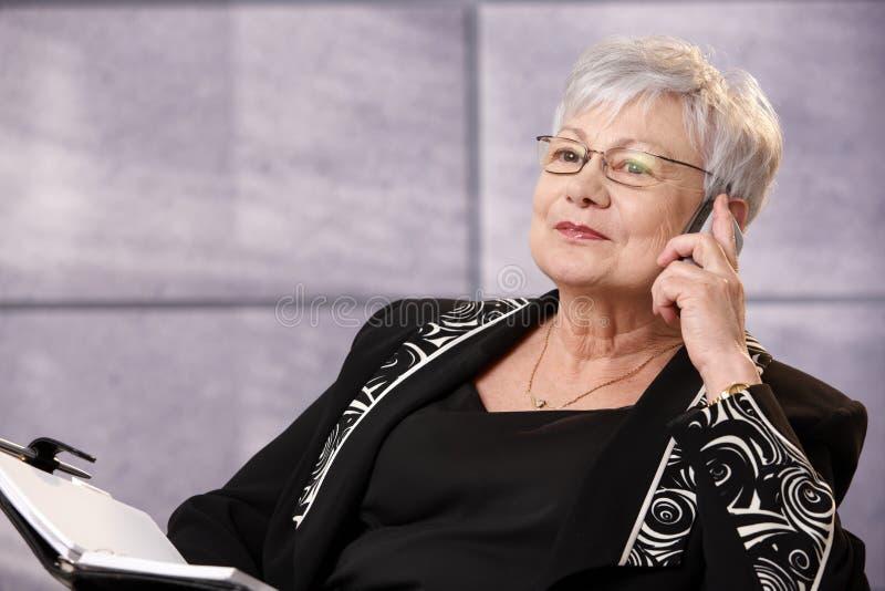 Ältere Geschäftsfrau, die Handy verwendet lizenzfreie stockfotos