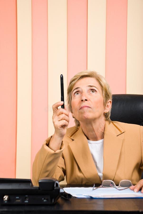 Ältere Geschäftsfrau, die oben mit Bleistift zeigt stockfotografie