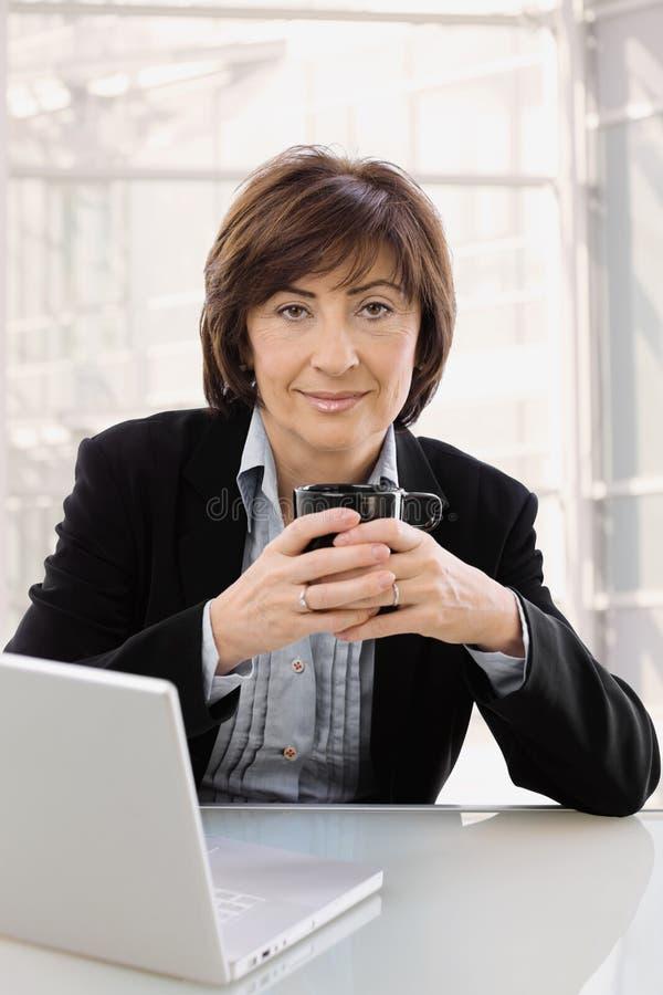 Ältere Geschäftsfrau, die am Schreibtisch sitzt lizenzfreie stockbilder