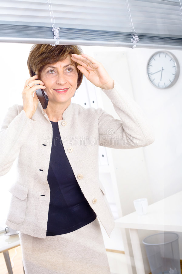 Ältere Geschäftsfrau, die um Telefon ersucht stockfotos