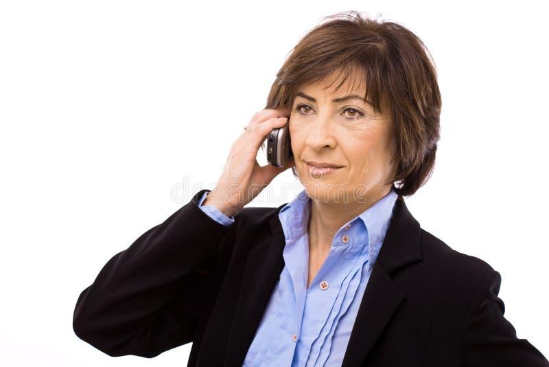 Ältere Geschäftsfrau, die um Telefon ersucht stockbilder