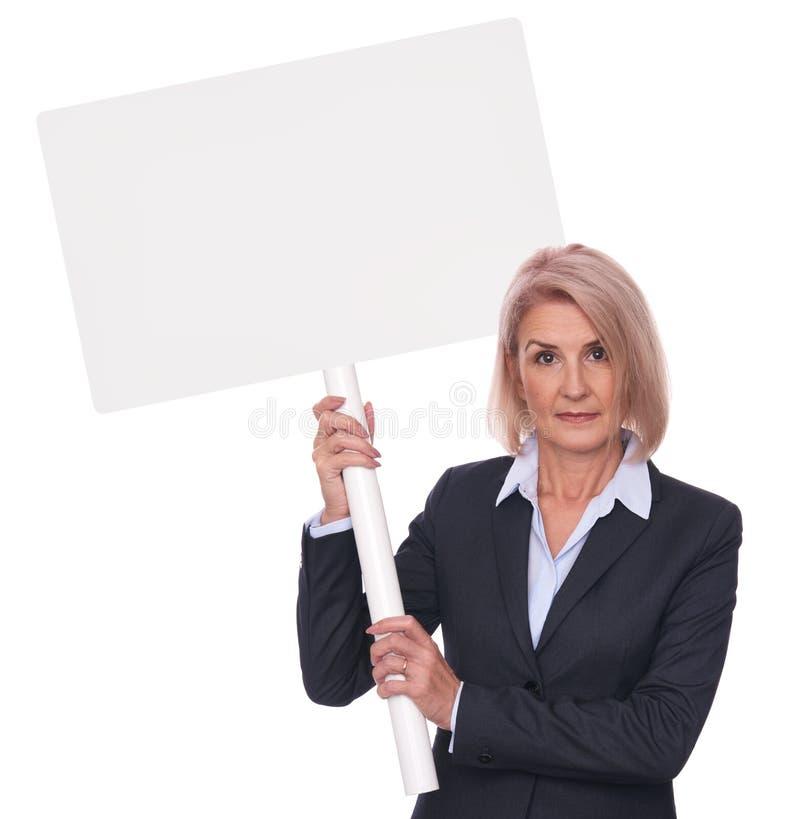Ältere Geschäftsfrau hält ein leeres Plakat lizenzfreie stockfotos