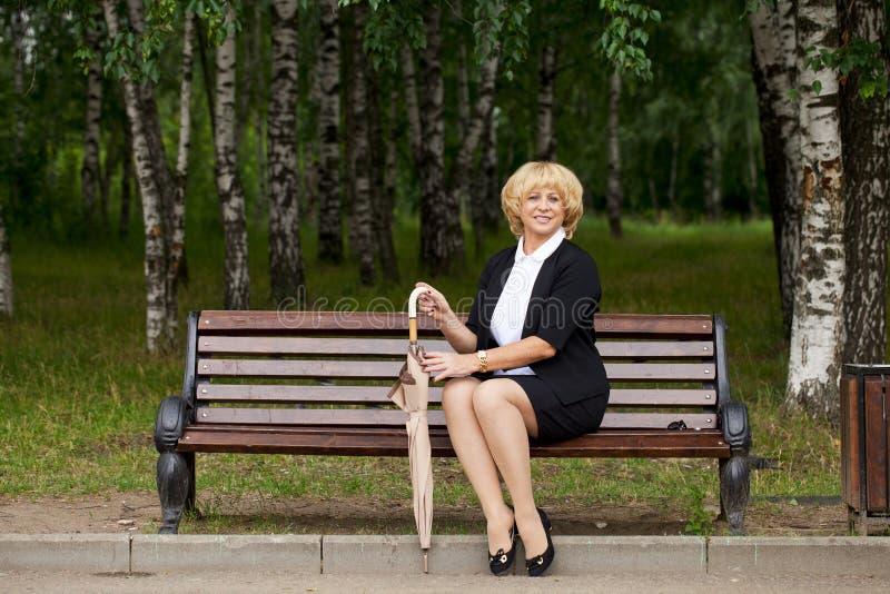 Ältere Geschäftsfrau in Jacke sittin auf Bank lizenzfreie stockbilder