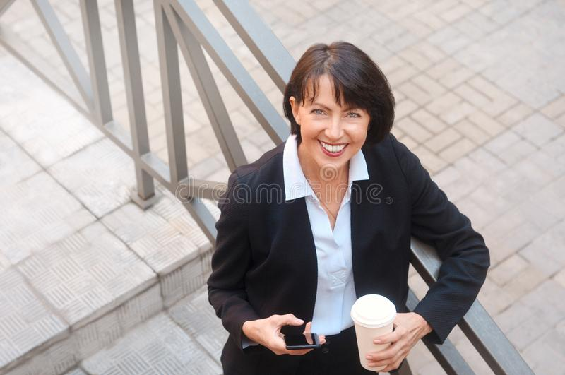 Ältere Geschäftsfrau mit Kaffee, unter Verwendung des Handys, im Freien stockfoto
