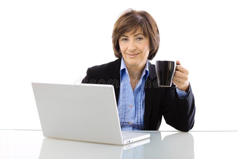 Ältere Geschäftsfrau trinkendes coffe stockfotografie