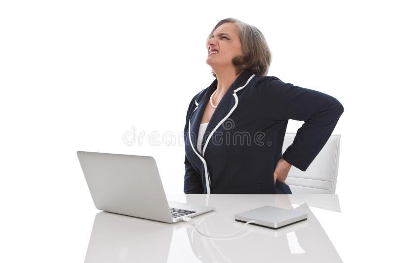 Ältere Geschäftsfraurückenschmerzen stockbilder