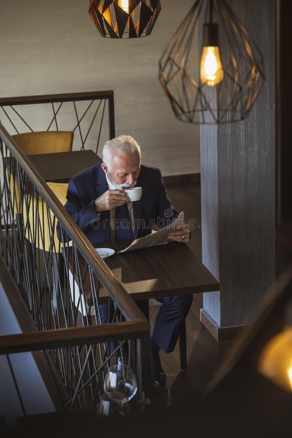Ältere Geschäftsmannlesezeitungen und trinkender Kaffee lizenzfreie stockfotos