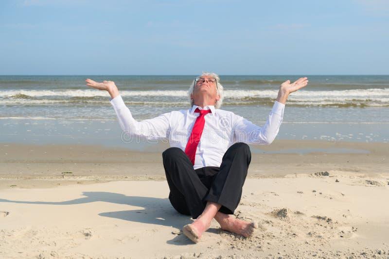 Ältere Geschäftsmannmeditation am Strand stockbilder