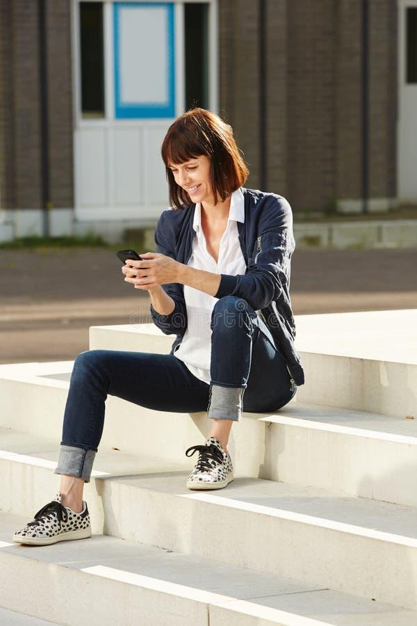 Ältere glückliche Frau, die auf Schritten mit intelligentem Telefon sitzt stockfotos