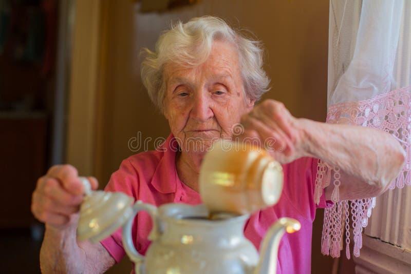 Ältere glückliche Frau, die Tee im Kessel macht lizenzfreie stockfotografie