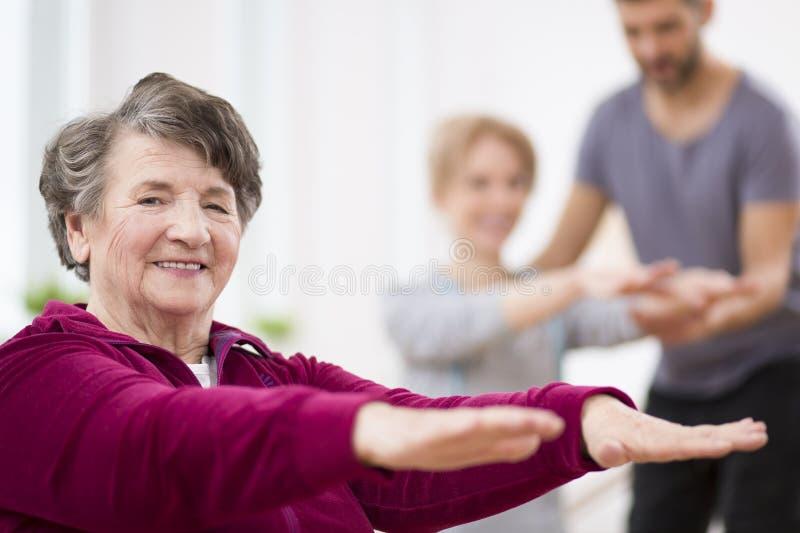 Ältere graue Frau, die in der Krankenhausphysiotherapiemitte trainiert stockbild
