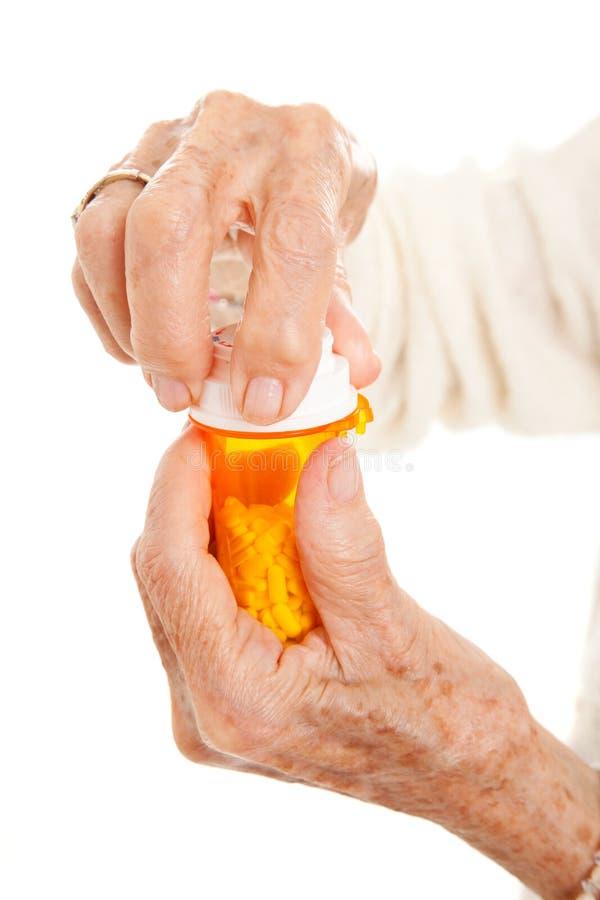 Ältere Hände auf Verordnung-Flasche stockfoto