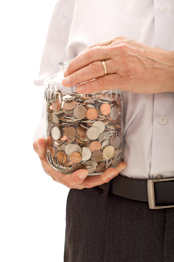 Ältere Hände, die Glas mit Lots Münzen anhalten stockfoto