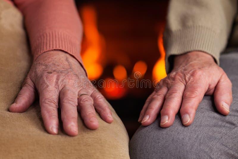 Ältere Hände, die nahe dem Kamin stillstehen lizenzfreies stockbild