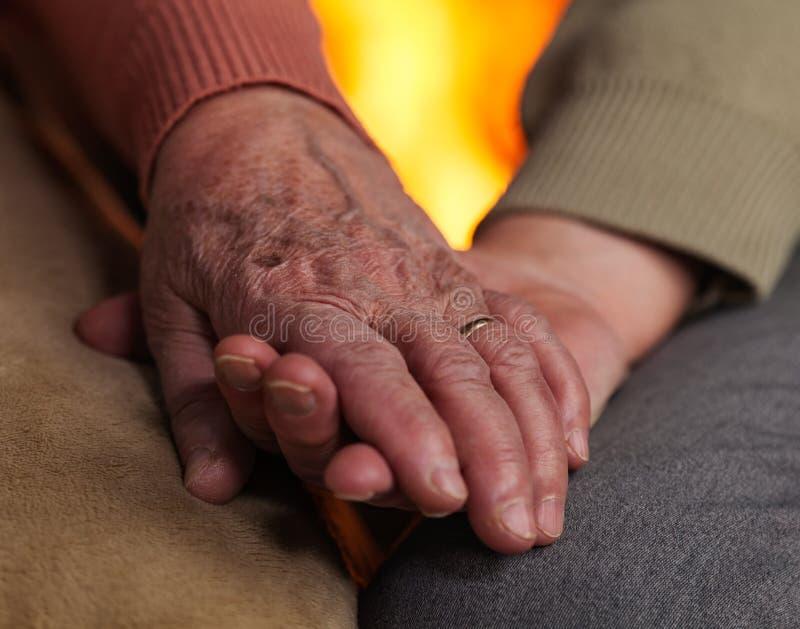 Ältere Hände, die sich halten stockfoto