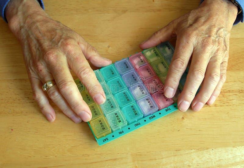 Ältere Hände mit Pillebehälter lizenzfreies stockbild